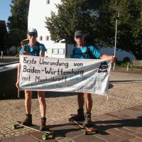 Ute Jansen und Markus Frommlet mit Longboards im Etappenziel Kressbronn
